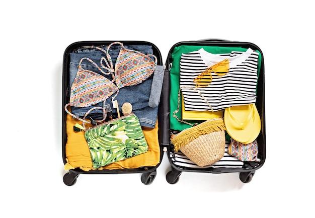 Flach lag mit offenem koffer mit freizeitkleidung für sommerferien über weißer wand. sommerferien, reisen, tourismus, fluggepäckkonzept. draufsicht
