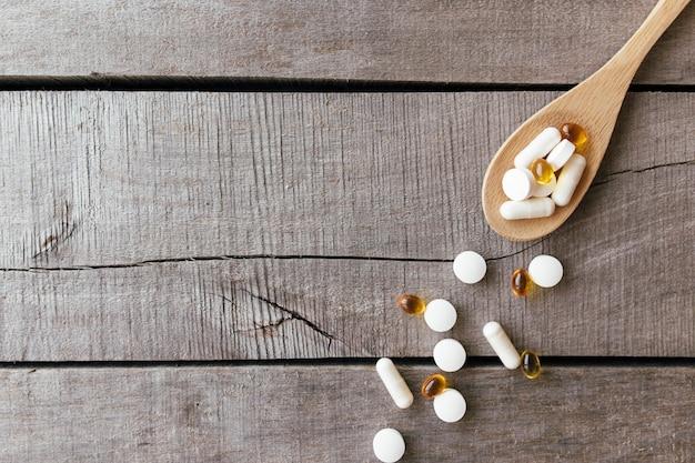 Flach lag mit omega 3 und vitaminzusätzen auf holzlöffel auf hintergrund. gesundheitskonzept. vitamin pillen.
