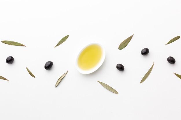 Flach lag olivenöl in untertasse mit blättern und schwarzen oliven