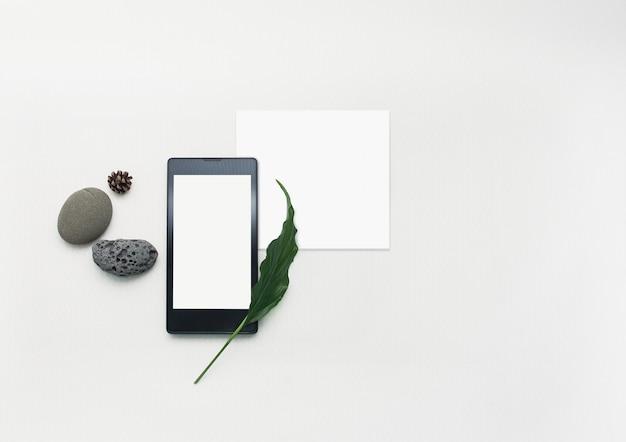 Flach lag smartphone, leeres briefpapier.