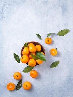 Flach lag süße und saftige mandarinen in einer holzschale und ein paar mandarinen auf blauem grund. draufsicht und kopierraum