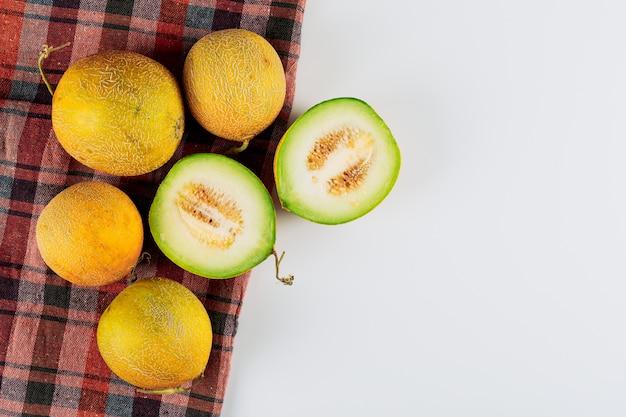 Flach lagen mehrere melonen mit in zwei hälften geteilter melone auf weißem hintergrund. horizontaler freier speicherplatz für ihren text