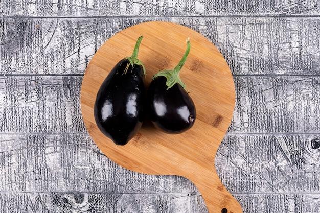 Flach legen 2 auberginen auf schneidebrett und grauem holzhintergrund. horizontal