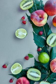 Flach legen früchte pfirsich, kiwi, himbeere, limette auf grauem papier, trendiger schatten und sonnenlicht, sonne, minimales sommerkonzept, kopierraum.