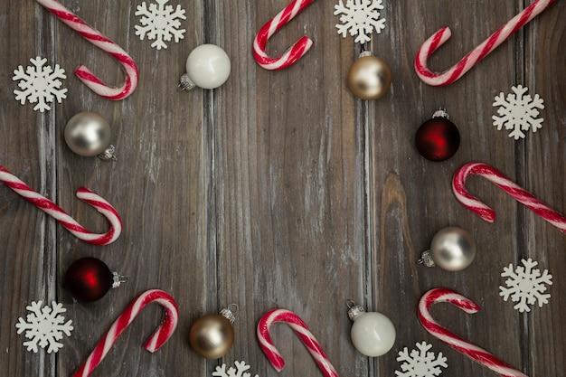 Flach legen kreisförmigen rahmen mit süßigkeiten und schneeflocken