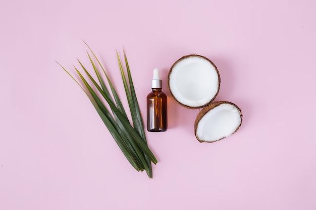 Flach legen mit geschnittenen hälften von kokosnuss und grünem palmblatt, glasflasche mit ätherischem öl. exotische frucht.