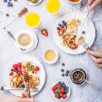 Flach legen mit scotch pancakes in blütenform, beeren und honig mit menschlichen händen.