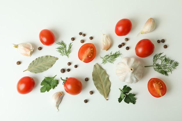 Flach legen mit tomaten, dill, pfeffer, knoblauch und lorbeerblättern auf weiß