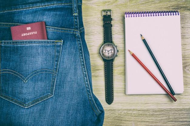 Flach legen notizbuch mit bleistiften, jeans, pass und armbanduhr