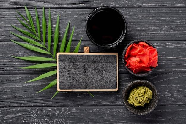 Flach legen sie ingwer wasabi und sojasauce schalen mit leeren notebook