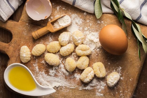 Flach legen sie ungekochte kartoffel-gnocchi auf schneidebrett mit eiern