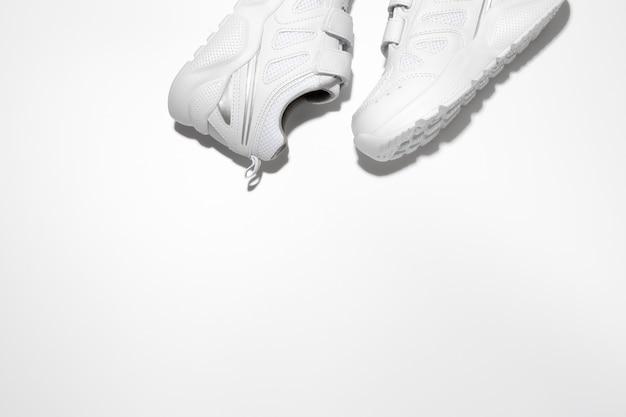 Flach legen sie zwei weiße unisex-sneaker an der seite oben mit freiem platz für text isoliert auf einem weißen ...