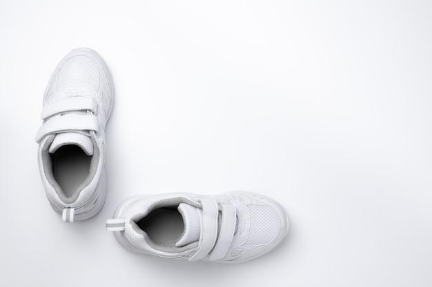 Flach legen sie zwei weiße unisex-sneaker mit klettverschlüssen in einem winkelwinkel zueinander isoliert...