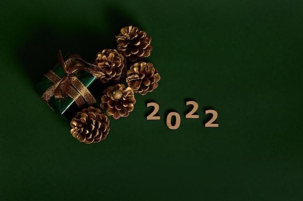 Flach liegen. goldene tannenzapfen, luxusgeschenk in glitzergrünem geschenkpapier mit goldener schleife und holzziffern 2022 einzeln auf dunkelgrünem hintergrund mit kopierraum für neujahrs- und weihnachtsanzeige