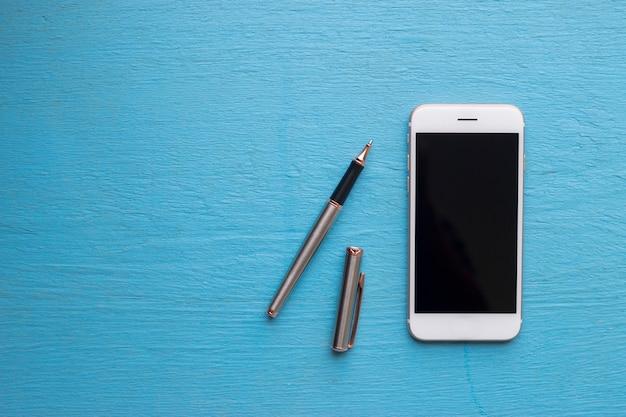 Flach liegen. intelligentes telefon und stift auf blauem hölzernem.