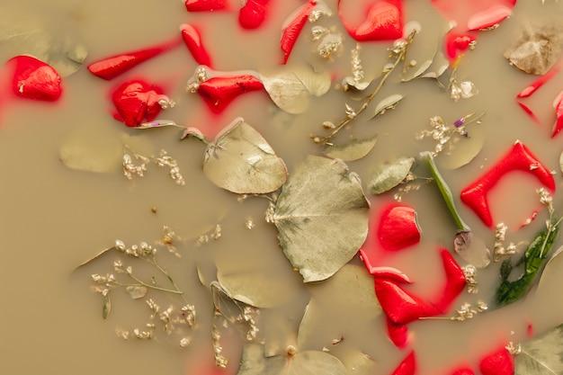 Flach liegen leuchtend rote blütenblätter in braunem wasser