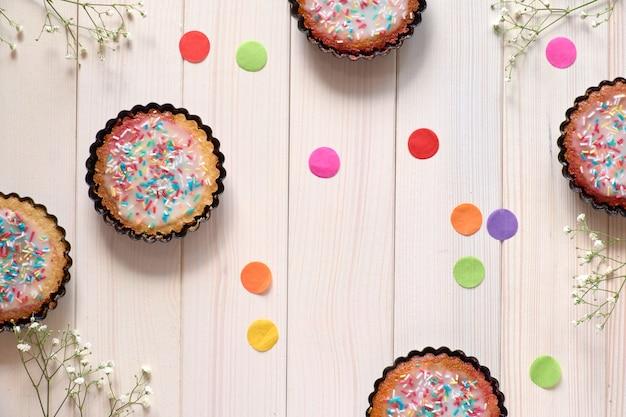 Flach liegen mit papierkonfetti und kleinen papageienkuchen mit bestreutem farbigem zucker auf weißem holz