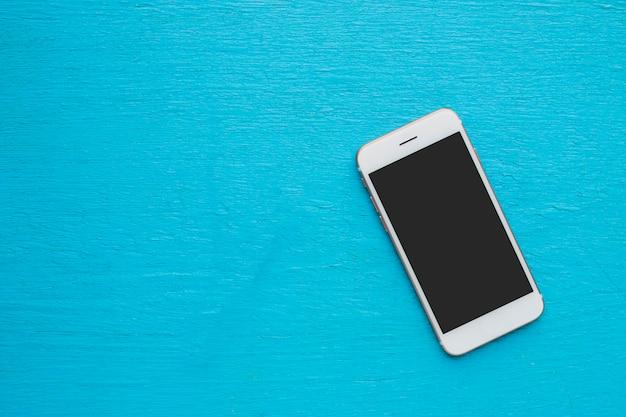 Flach liegen. smartphone auf blauem holz.