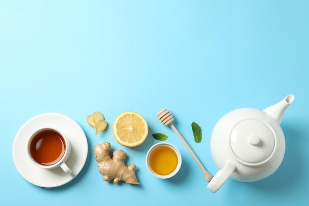 Flach liegen. tasse tee, teekanne, zitrone, ingwer, minze, honig und schöpflöffel auf blau, kopierraum