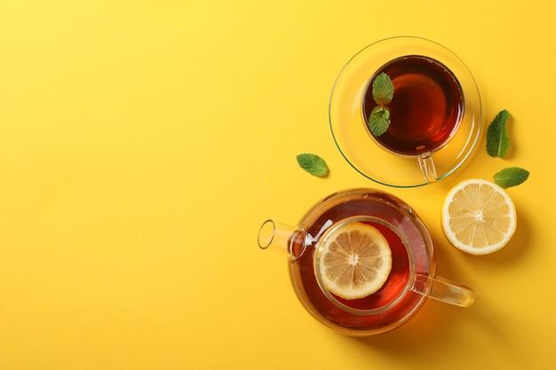 Flach liegen. tasse tee, teekanne, zitrone und minze auf gelb, kopierraum