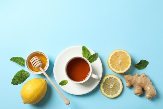 Flach liegen. tasse tee, zitrone, ingwer, minze, honig und schöpflöffel auf blau, kopierraum