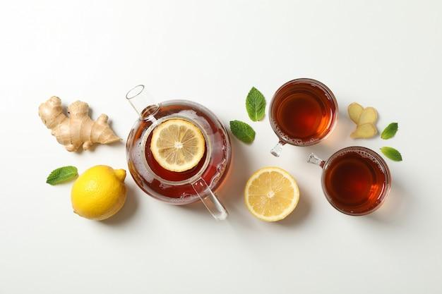 Flach liegen. tassen mit tee und teekanne, zitrone, minze und ingwer, platz für text