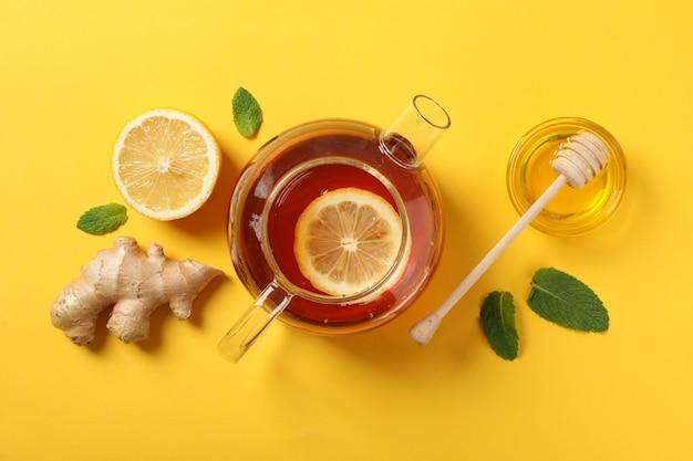 Flach liegen. teekanne, zitrone, ingwer, minze, honig und schöpflöffel auf gelb, kopierraum