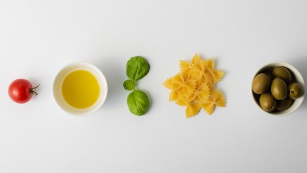 Flach liegen ungekochte farfalle tomaten und oliven