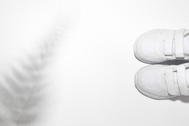 Flach liegen zwei weiße kindersneaker mit klettverschlüssen mit schatten von einem farn- oder palmenisolat...