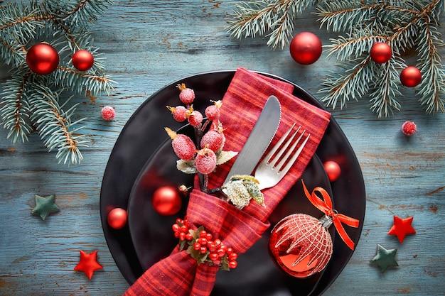 Flach liegend mit weihnachtsdekorationen in grün und rot mit gefrosteten beeren, schmuckstücken, tellern und geschirr