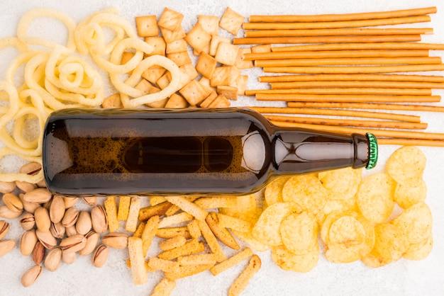 Flach liegende bierflasche und snacks