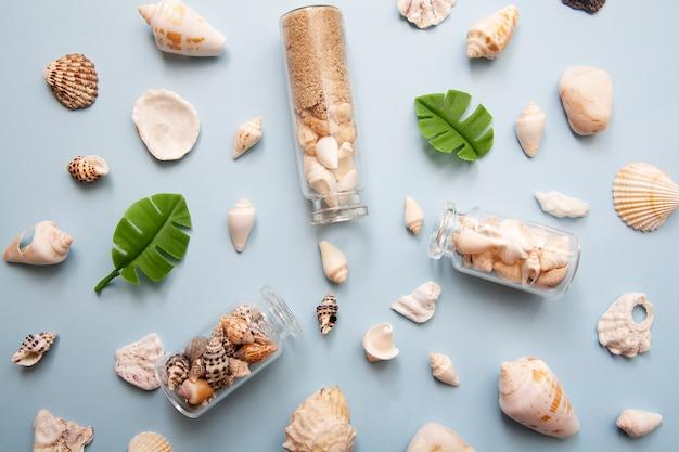 Flach liegende muscheln, miniflaschen, tropische blätter, strohhut. das konzept des meeres, urlaub, reisen