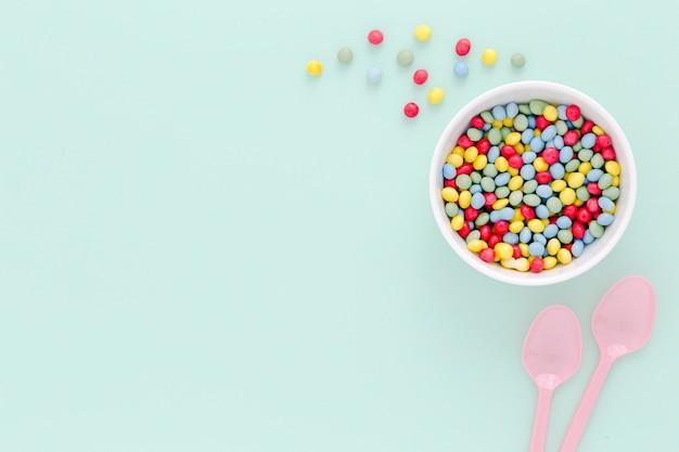 Flach liegende plastiklöffel und süßigkeiten