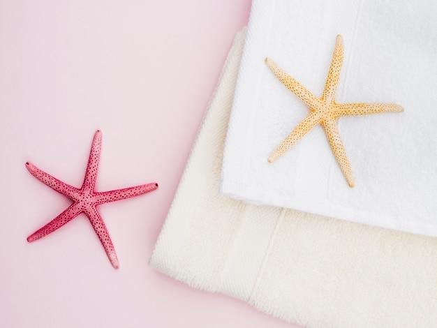 Flach liegende seesterne und handtücher