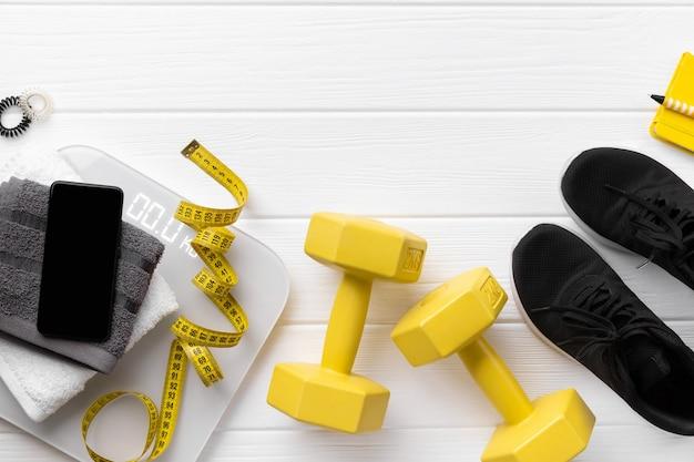 Flach liegende sportgeräte, turnschuhe und smartphones mit draufsicht auf holzoberfläche