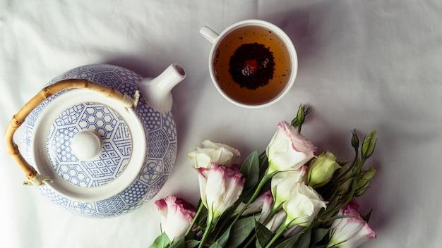 Flach liegende teetasse und teekanne