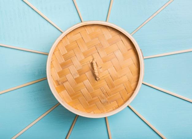 Flach liegender bambus-dampfgarer mit essstäbchen