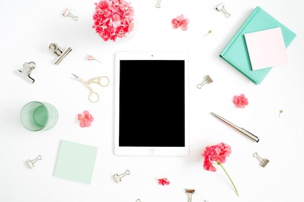 Flach liegender mode-schreibtisch. weiblicher arbeitsbereich mit leerem bildschirmtablett, roten blumen, zubehör, minztagebuch auf weiß