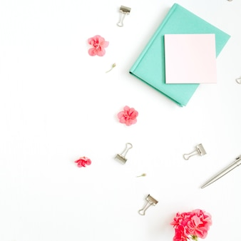 Flach liegender mode-schreibtisch. weiblicher arbeitsbereich mit roten blumen, zubehör, minztagebuch auf weiß