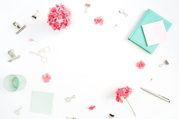 Flach liegender mode-schreibtisch. weiblicher rahmenarbeitsbereich mit roten blumen, zubehör, minztagebuch