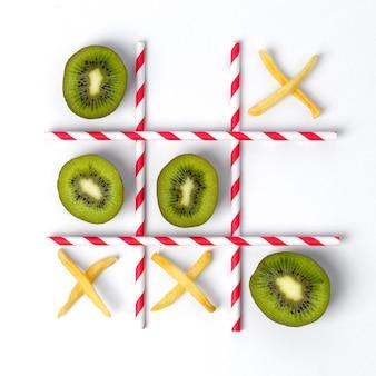 Flach liegender tic tac toe aus kiwi, pommes und strohhalmen.