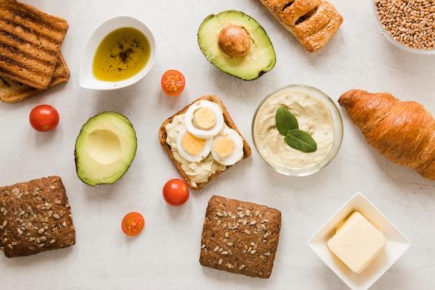 Flach liegender toast mit hummuseiern und avocado