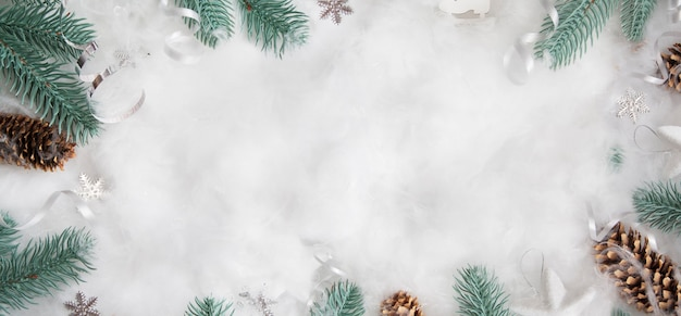 Flach liegender winterkopf: fichtenzweige im schnee mit weihnachtsdekoration mit kopierraum
