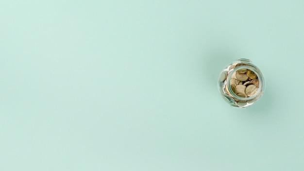 Flach liegendes glas mit münzen
