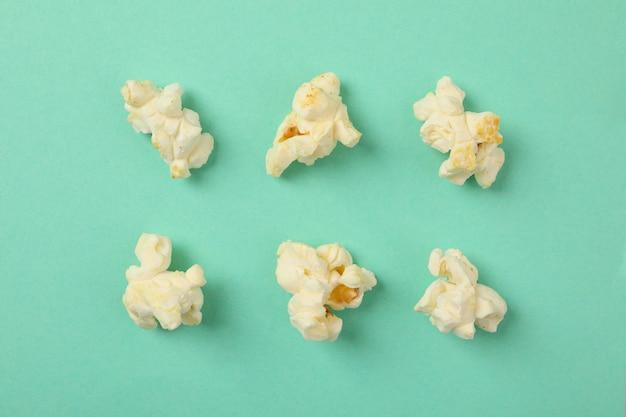 Flach mit popcorn auf minzfläche liegen. essen fürs kino