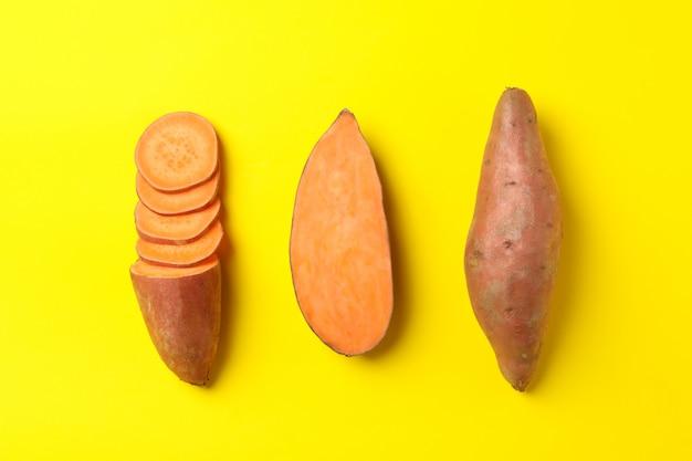 Flach mit süßkartoffeln auf gelbe oberfläche legen