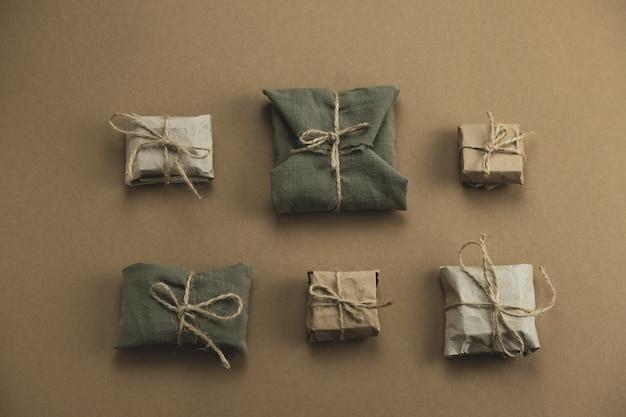 Flach verlegte geschenkboxen aus textil und kraftpapier auf braun