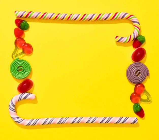 Flache anordnung der bonbons auf gelbem hintergrund mit kopienraum