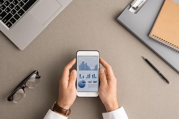 Flache anordnung der hände des jungen modernen wirtschaftswissenschaftlers oder buchhalters, der smartphone mit finanzdaten auf dem bildschirm hält, während sie es analysiert