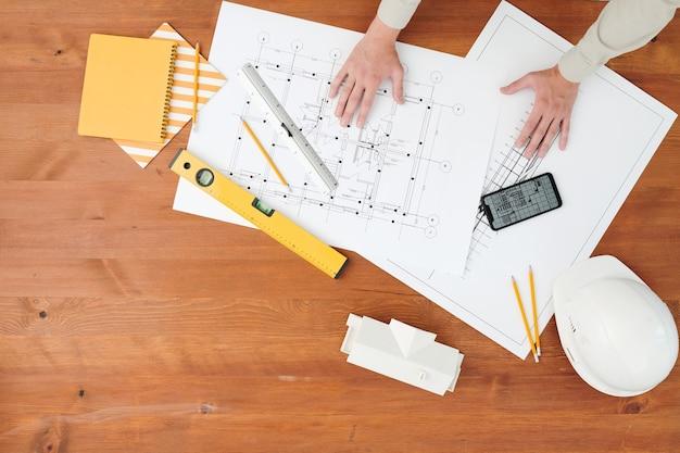 Flache anordnung der hände des jungen zeitgenössischen ingenieurs oder vorarbeiters über abgewickelten bauplänen mit skizzen des neuen projekts am arbeitsplatz
